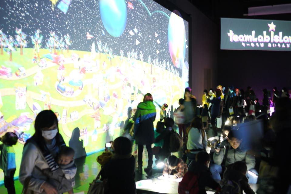 子どもたちが描いた絵がスキャンされ、巨大プロジェクタに投影され、喜ぶ親子たち。